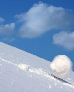 Snow ball slides downhill and speeds up.