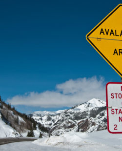 A convertible sign alerts winter travelers to possible snow slides in the Rocky Mountains of southwest Colorado.