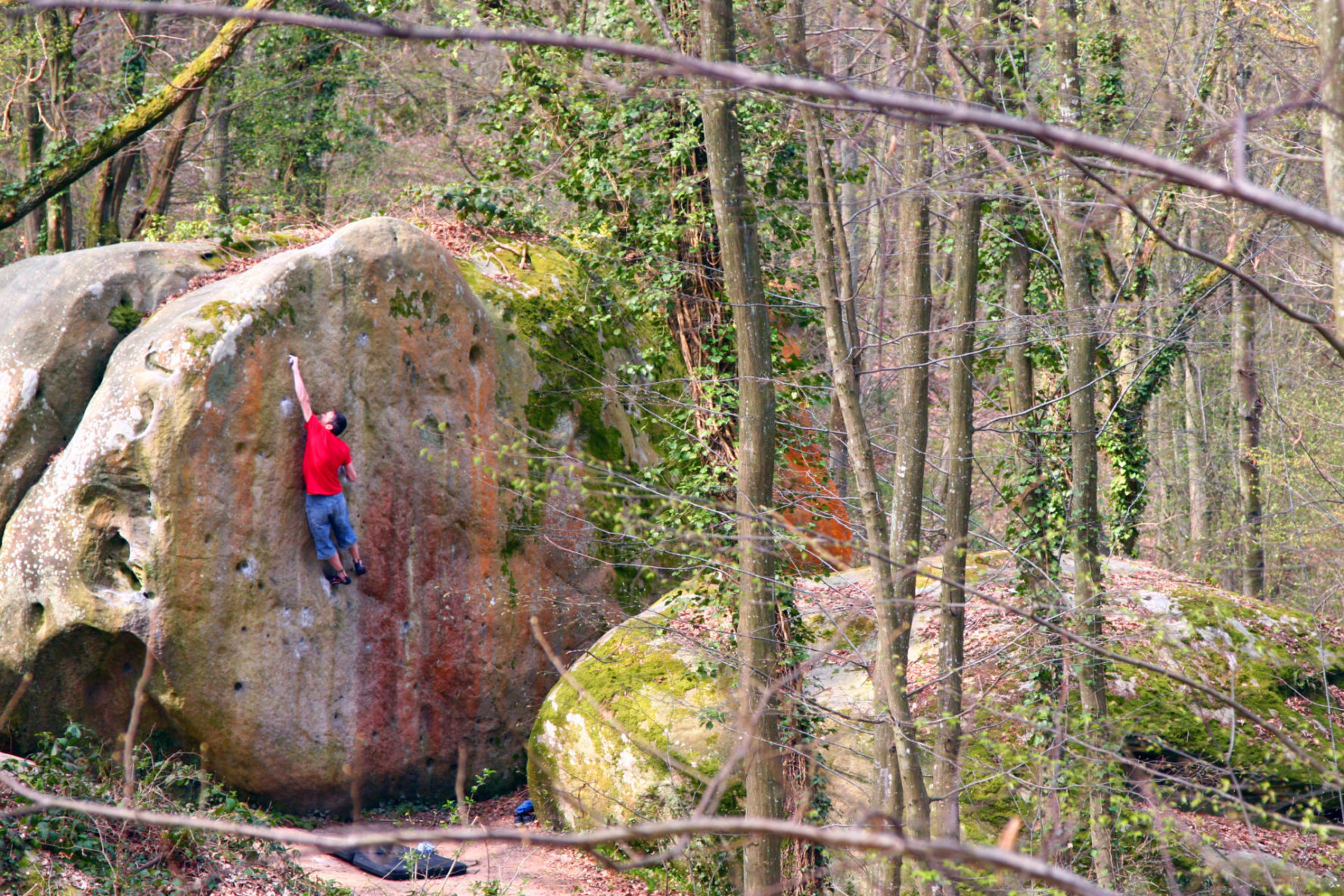 Dude climbing a big rock in France