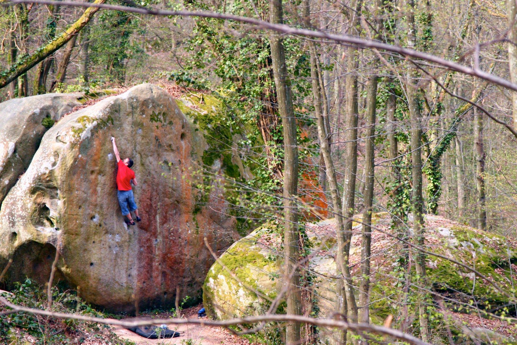 Dude climbing a big rock in France