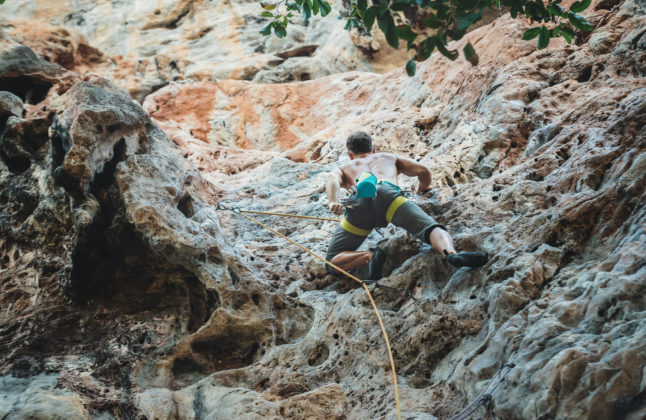 Mountain climber climbing on Climbing Route using rope on Tonsay beach in Krabi, Thailand.