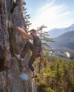 Male Rock climber climbing on the edge of the cliff during a sunny winter sunset. Taken in Area 44 near Squamish and Whistler, North of Vancouver, BC, Canada.