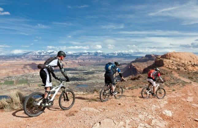 3 people riding a mountain bike in Moab, Utah