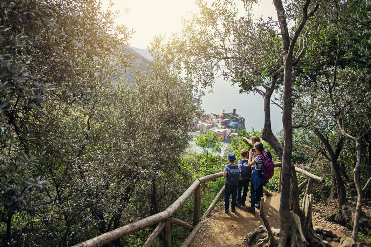 Family hiking in trails of Cinque Terre - a UNESCO World Heritage Site. The family is looking from the distance at the beautiful city of Vernazza.