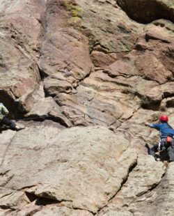 Pair of mountain climbers work together to scale a cliff high in the Colorado Rockies.