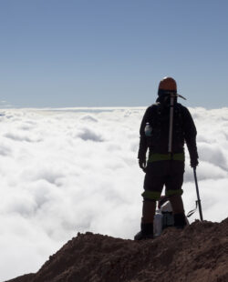 Mountain climber in Cotopaxi descending into a sea of clouds and Antisana volcano in the background, Andes Ecuador