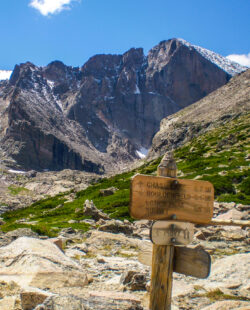 Longs Peak with trail map scene guiding your way many people die climbing this mountain. Estes Park , Colorado is near the Long Peak many many people attempt to climb this Peak and some do not survive. This shows the peak in Summer on a perfect day to climb. A colorado 14er