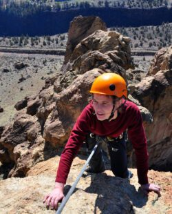 A woman nears the top of a spire at Smith Rock State Park, Oregon. The Crooked River is far below in the valley.