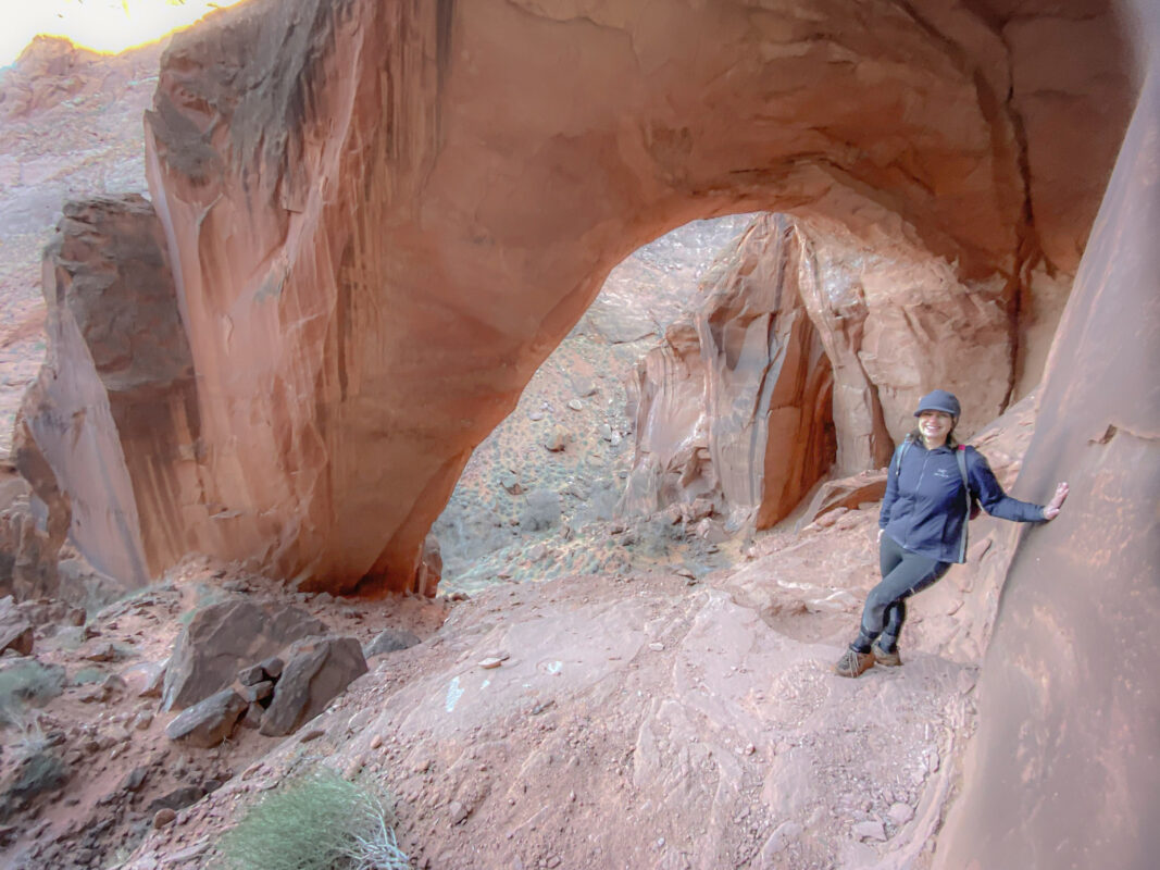 Woman hiking under the Wrather Arch