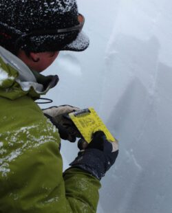 Avalanche Education in Crested Butte, a man measures snow