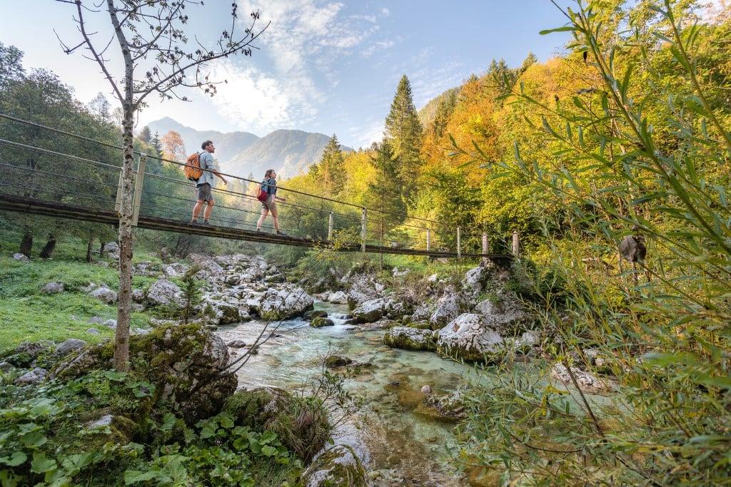 Hiking across a bridge over Soca, Alpe Adria Trail