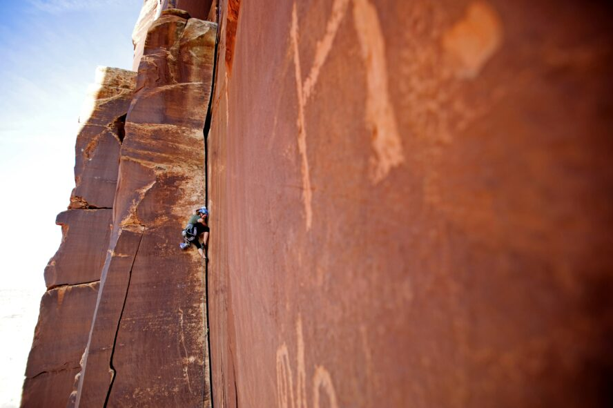 A climber on Amaretto Corner in Indian Creek, a Wingate sandstone splitter that starts as perfect hands and gets progressively wider. The route shows wear from usage and is not far from historic petroglyphs.