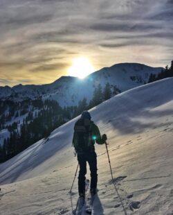 A skier enjoying the dawn from Telluride's snowy backcountry
