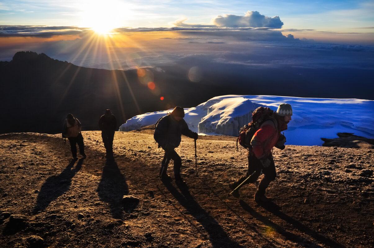 """The rising sun breaks through the clouds as climbers near the summit of Mt. Kilimanjaro, Tanzania."""