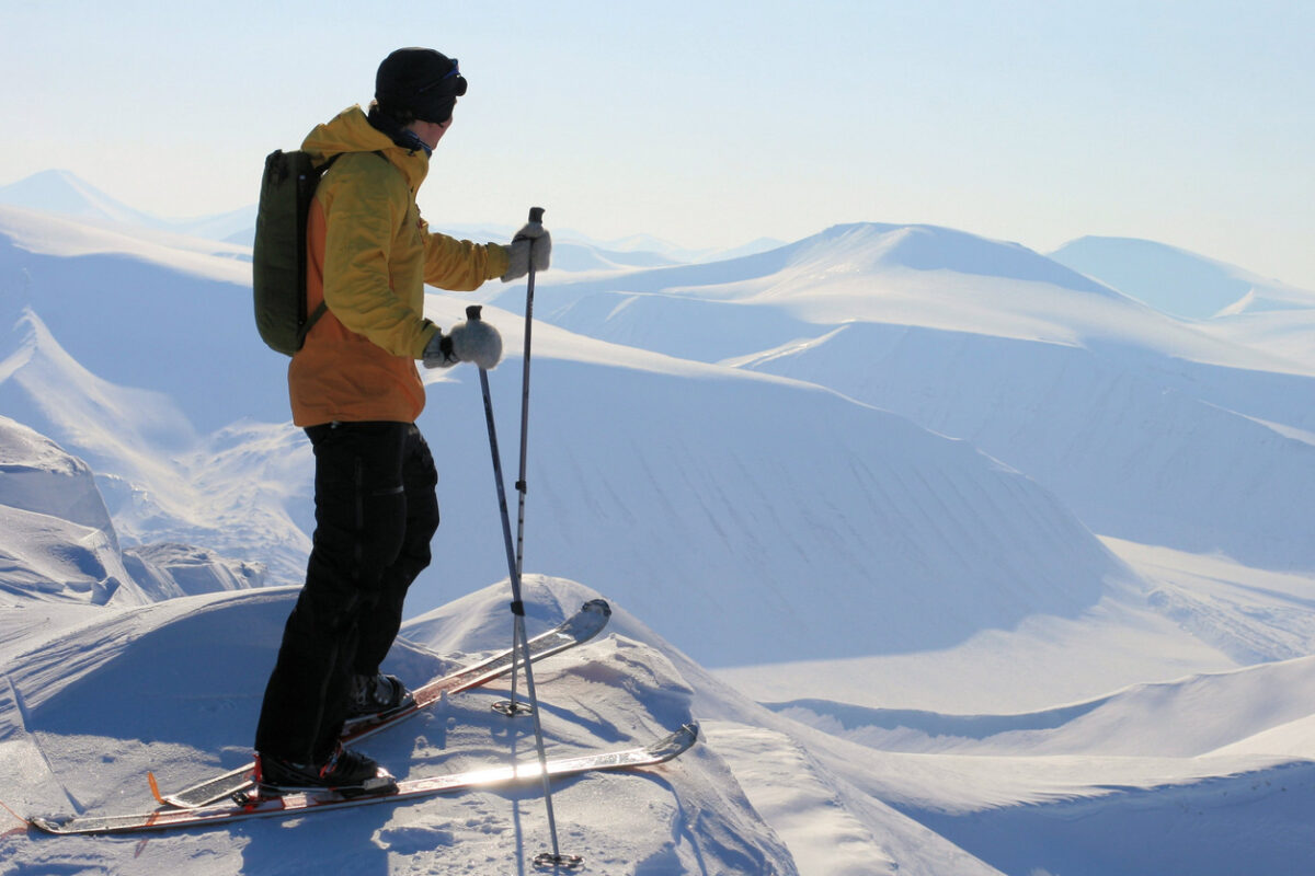 A skier enjoying the view over the snowy peaks and valleys in Svalbard