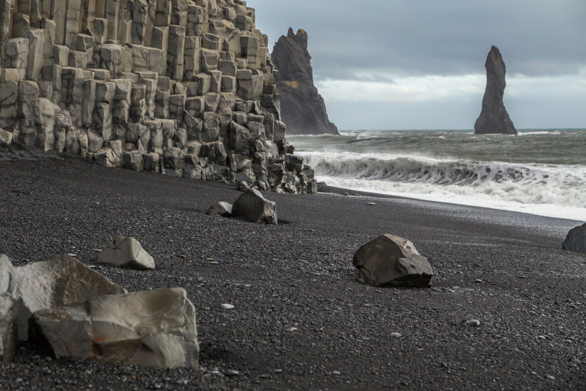 Basalt rock formations on the volcanic black sand beach at Vik in Iceland. The cliff face is columns of hexagonal rocks. Rock stacks are in the sea. Large waves and spray is being whipped up from the ocean. Rocks lie on the sand and the sky is cloudy and moody.