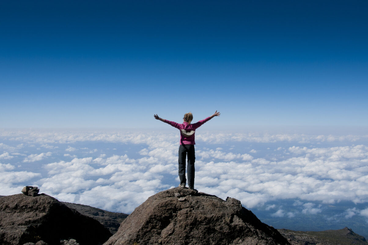 A happy trekker above the clouds on the route to the summit of Kilimanjaro