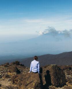 Woman traveler relaxing after the hiking trip feeling success enjoying the view of the Meru mountain from the Mount Kilimanjaro, Tanzania